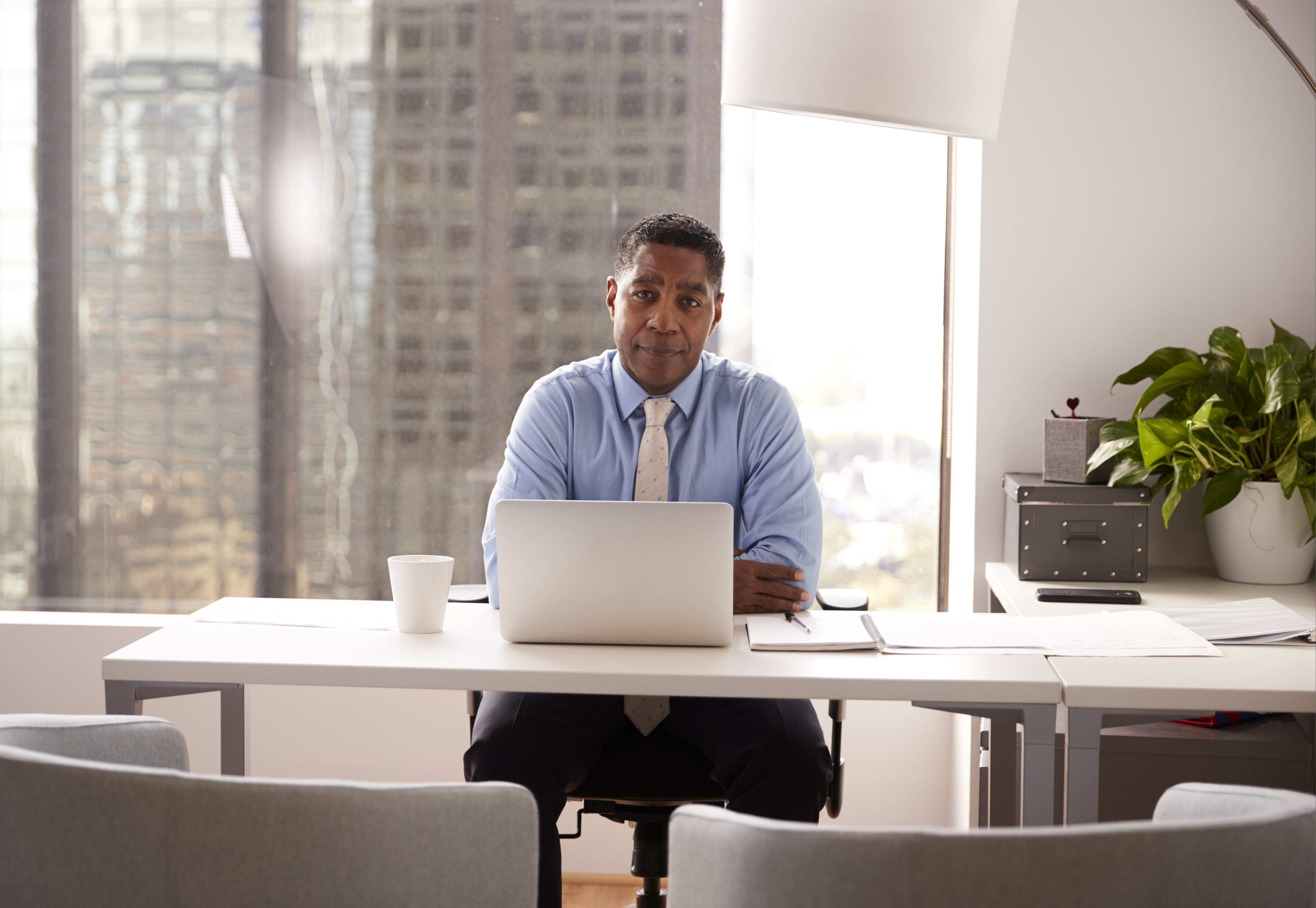 Portrait Of Male Financial Advisor In Modern Office Sitting At Desk Working On Laptop - Tributus